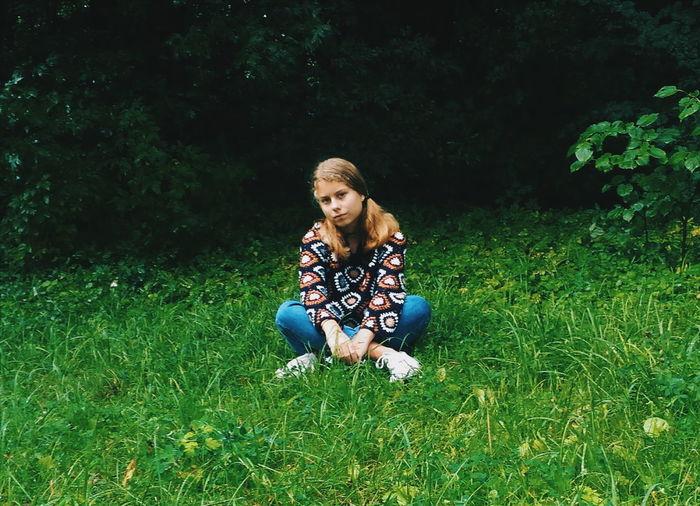 Full length of girl sitting cross legged on grassy field
