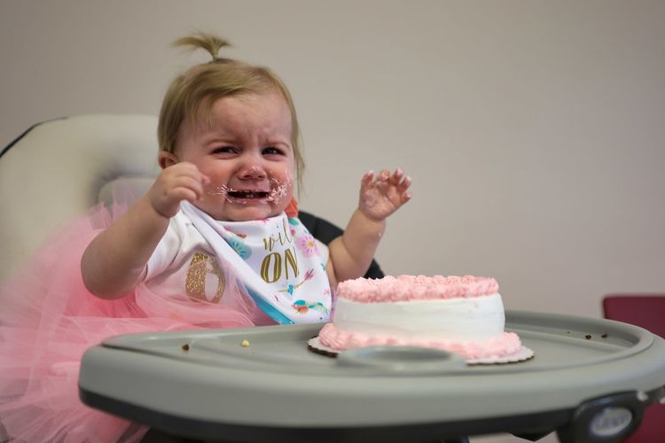 Cute baby girl crying while sitting with birthday cake on high chair at home