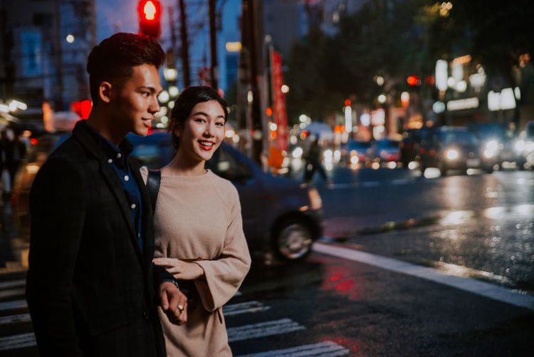 Young couple standing on street in city at night