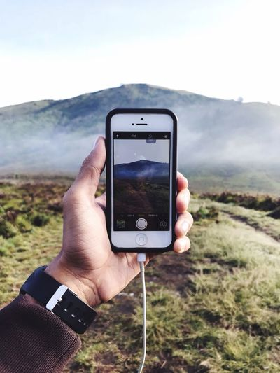 Close-up of man hand photographing mountain with smart phone