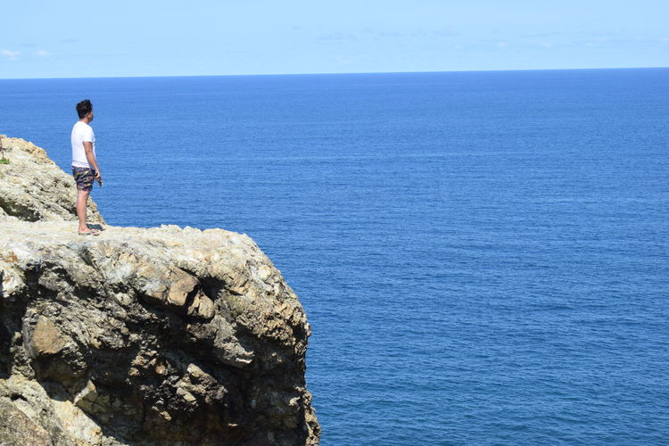 Side View Of Man Looking At Sea While Standing On Rock Formation