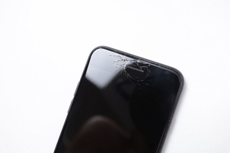 Broken glass smartphone isolated copy space Studio Shot Close-up White Background Indoors  No People Copy Space Still Life Single Object Black Color High Angle View Simplicity Transparent Technology Creativity White Color Activity Communication Broken Glass IPhone