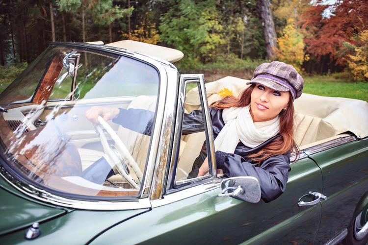 Woman Wearing Cap Driving Convertible Car Against Trees