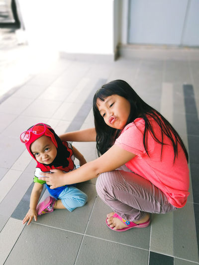 High angle view of cute sisters on tiled floor