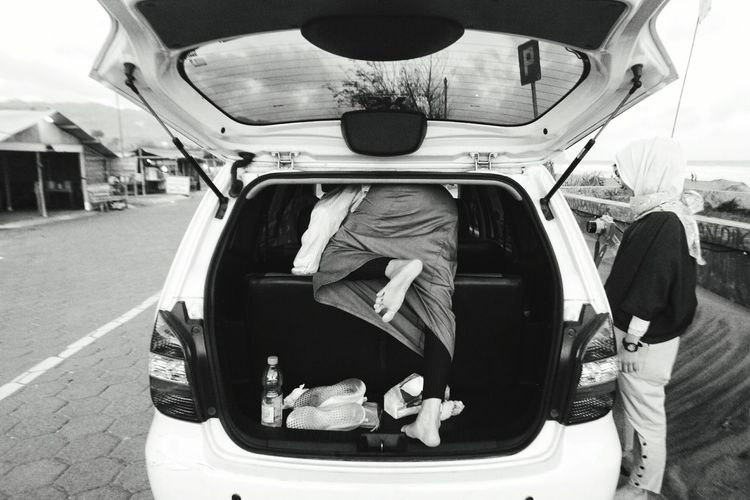 Rear view of woman entering car trunk on road