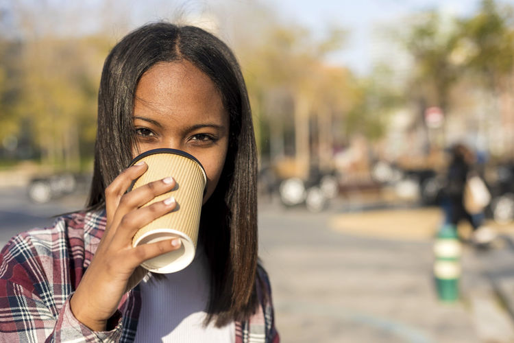 Young african american woman standing in city street while holding a take away coffee and looking camera in a sunny day Portrait One Person City Young Adult Holding Food And Drink Headshot Focus On Foreground Cup Drinking Adult Drink Young Women Incidental People Looking At Camera Coffee - Drink Coffee Cup City Life Hairstyle Outdoors Take Away Relaxing Sitting Laugh Laughing Sunny Daylight