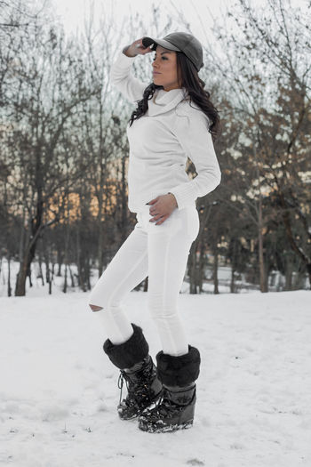 Side View Of Young Woman In Warm Clothing Standing At Snow Covered Forest