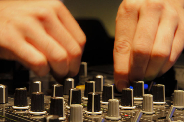 Cropped Image Of Dj Mixing With Audio Control Equipment