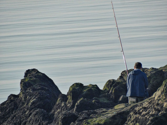 Fisherman. Real People Rear View One Person Lifestyles Men Leisure Activity Rock Rock - Object Nature Solid Water Beauty In Nature Day Casual Clothing Scenics - Nature Standing Sea Rod Outdoors Fishing Fisherman Man