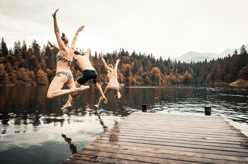 People jumping by lake against sky