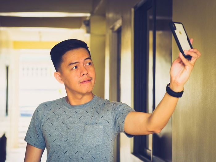 Man Taking Selfie On Mobile Phone At Home