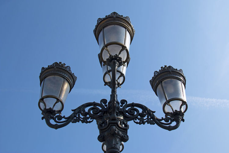 Low angle view of lamp against blue sky