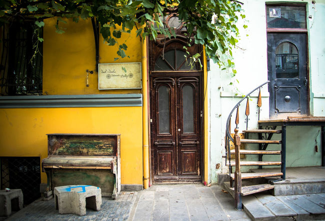 Play to enter Architecture Building Exterior Built Structure City Day Doors Georgia No People Old Piano Old-fashioned Outdoors Piano Stairway Steps Tbilisi Tree Yellow Color