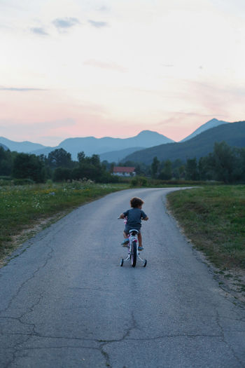 Rear view of boy riding bicycle on road against sky