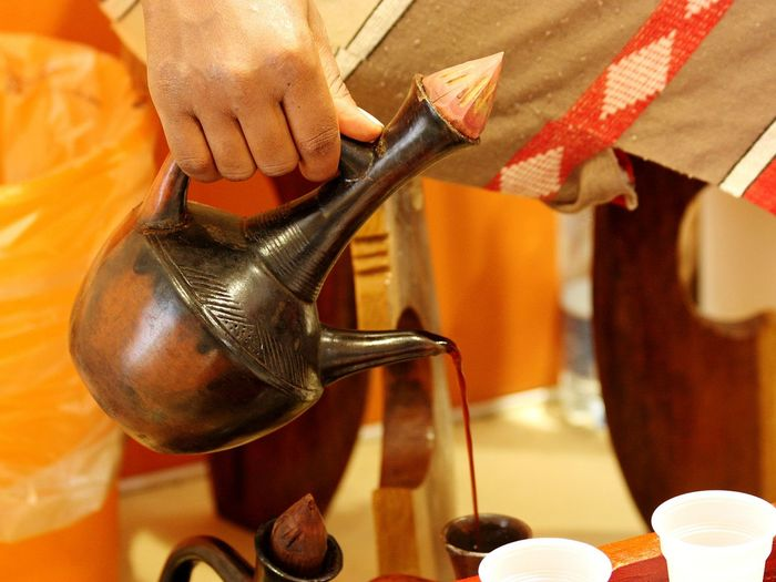 Cropped image of person pouring coffee in traditional container