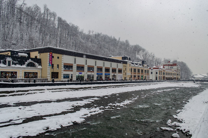 Snow covered railroad tracks by buildings against sky