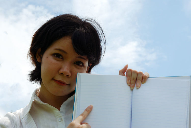 Portrait of woman showing empty book against sky