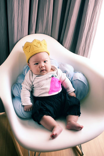 Cute Baby Girl Sitting On Armchair At Home