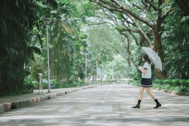 Side view of young woman with umbrella walking on road