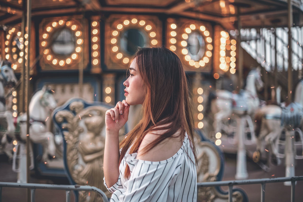 Woman looking away while standing by carousel
