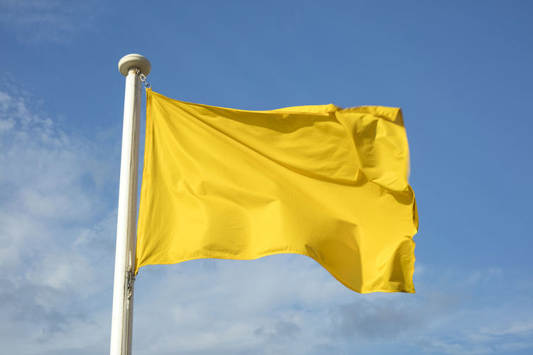 Close up of yellow flag at the beach, warning of sea conditions to bathers. Caution Caution Sign Holidays Summertime Tourist Beach Blue Danger Environment Flag Pole Sky Summer Sunlight Tourism Warning Warning Sign Waving Wind Yellow Yellow Color Yellow Flag