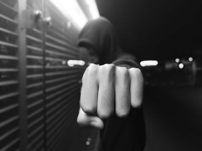 Close-up of man with clenching fist at night