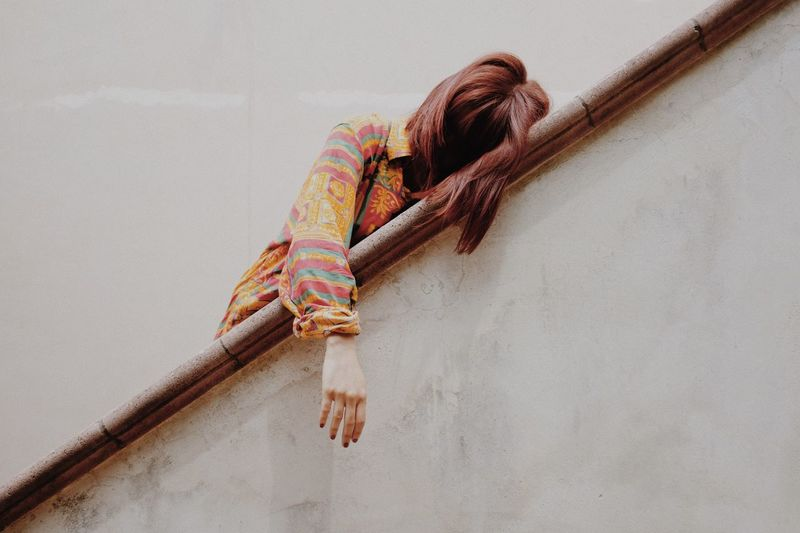Low Angle View Of Woman Leaning On Railing Against White Wall