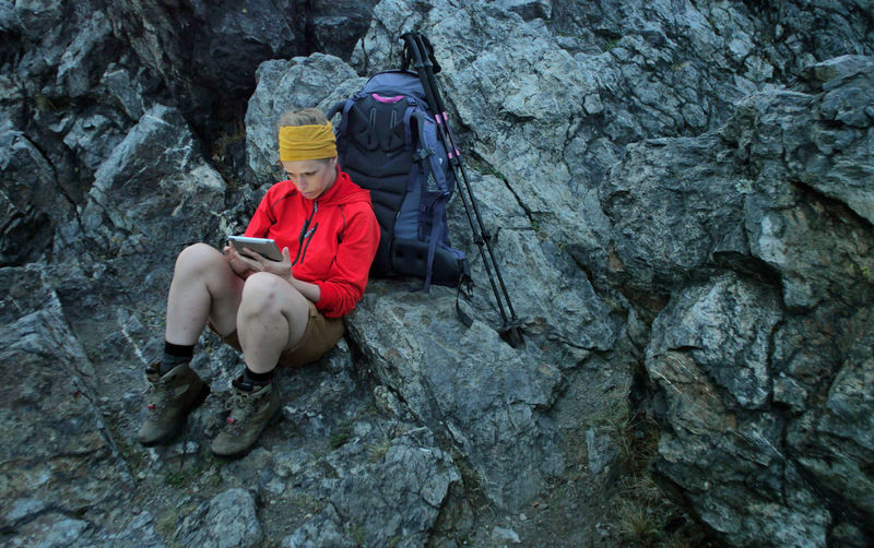 High Angle View Of Hiker Using Digital Tablet On Rocky Mountain
