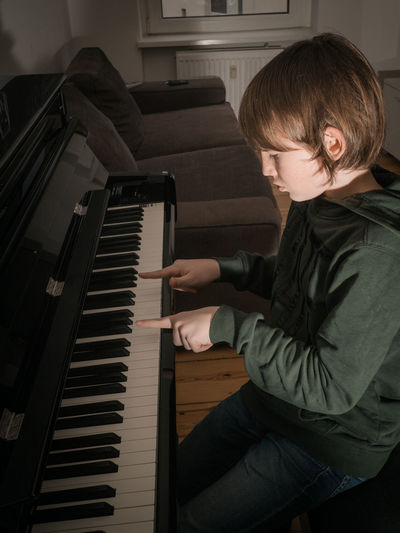 High angle view of boy playing piano at home