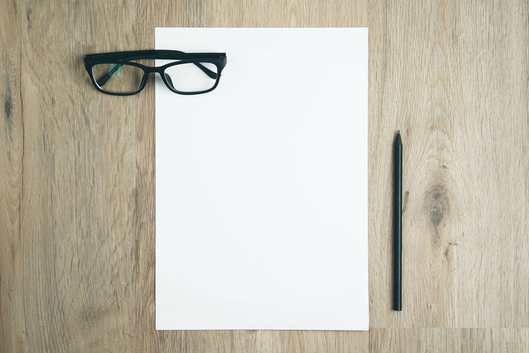 Blank paper on top of wood table with black pencil. Paper A4 Top View Flat Lay White Blank Copy Space Pencil Desk Table Glasses Minimalism Hipster Writing Writer Wooden Drawing Space Blogger Written Wood - Material Vintage Workspace Office Top High Angle View Message Document Accessories Education
