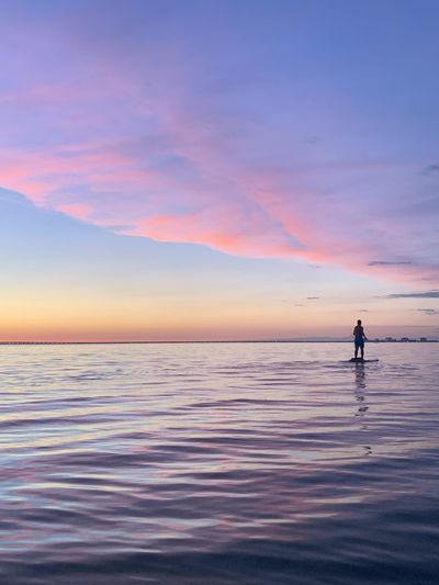 Man paddleboarding on lake against sky