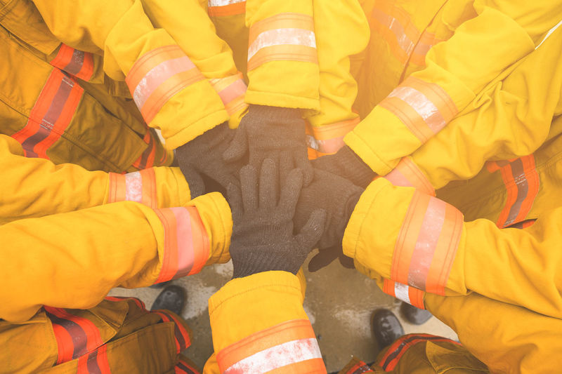 High angle view of firefighters with gloves stacking hands in unity