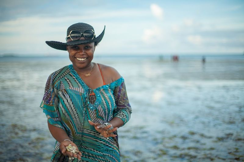 Portrait of smiling woman showing seashells while standing on beach