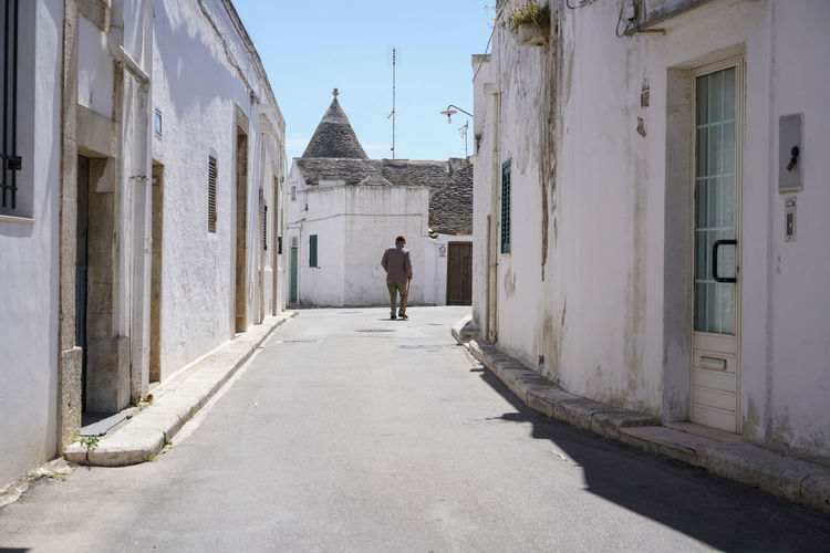 Rear View Of Man Walking On Road Amidst Old Houses In Town