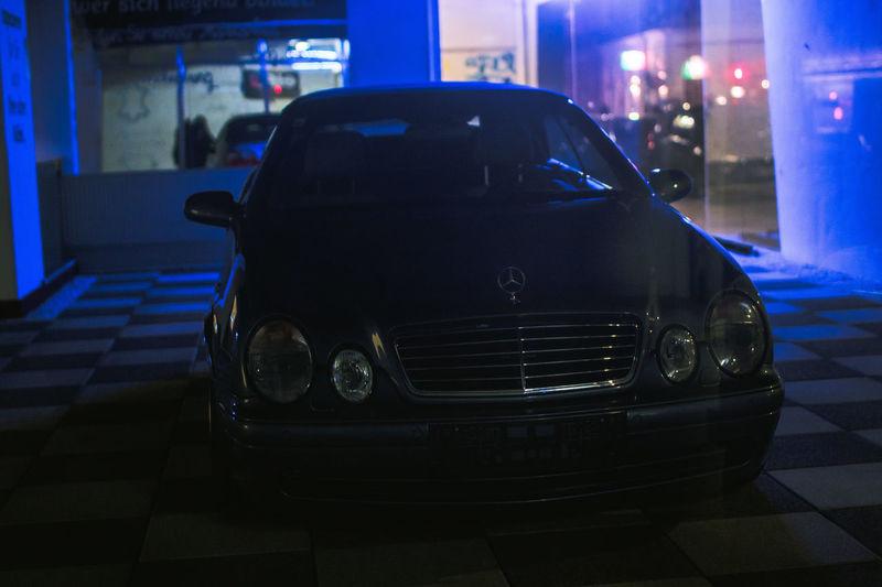 Close-up of car on illuminated street at night