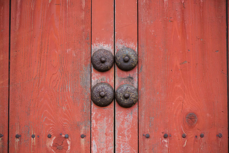 Close up of a pair of old wooden doors, red paint peeling away, with four rusting metal studs in the centre. Abstract Architecture ASIA Close-up Door Japan Old Old Buildings Peeling Paint Red Color Red Door Rustic Rusty Metal Symmetry Traditional Wood Door Wooden Colour Your Horizn The Architect - 2018 EyeEm Awards