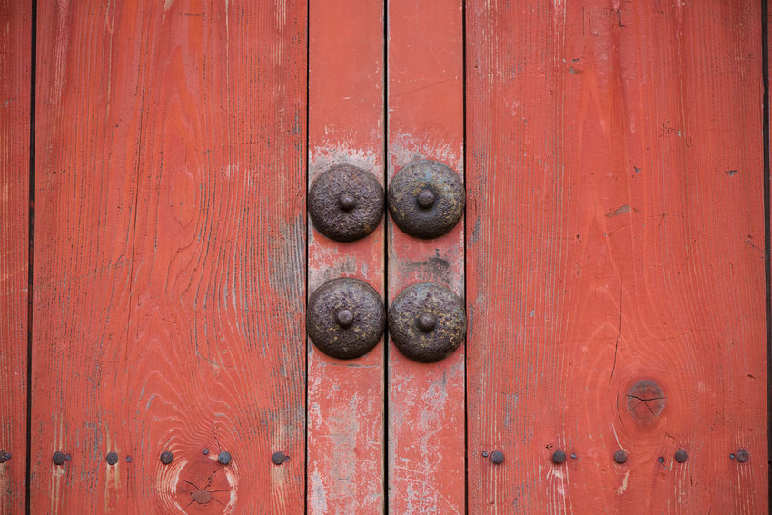 Close up of a pair of old wooden doors, red paint peeling away, with four rusting metal studs in the centre. Abstract Architecture ASIA Close-up Door Japan Old Old Buildings Peeling Paint Red Color Red Door Rustic Rusty Metal Symmetry Traditional Wood Door Wooden Colour Your Horizn