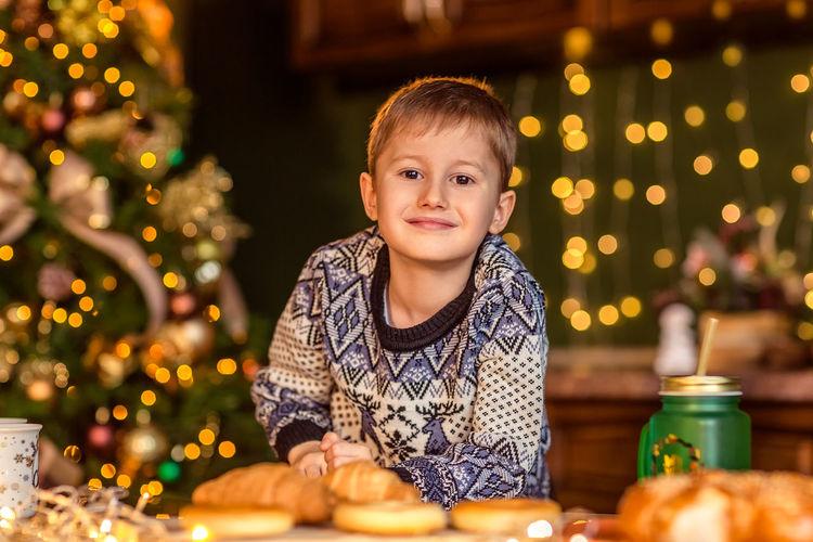 Portrait of smiling girl sitting on illuminated christmas tree