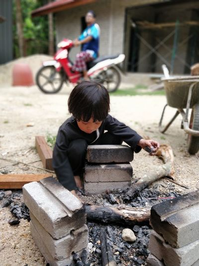 Boy Crouching At Campfire On Field