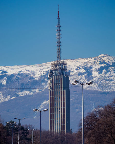 Communications tower on snowcapped mountain against blue sky