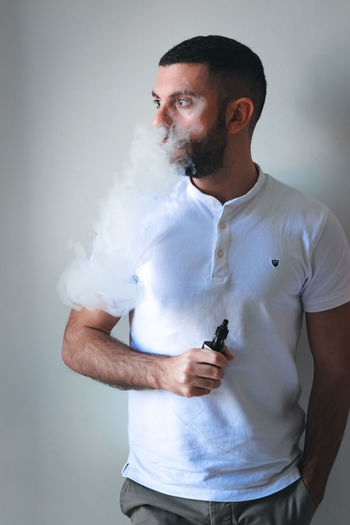 E-Cigarettes EyeEm Best Shots EyeEm Selects EyeEm Gallery E-Cigarette Technology Smoke One Person Holding Front View Indoors  Young Men Casual Clothing Men Communication Standing Beard Facial Hair Young Adult Smoke - Physical Structure Waist Up Studio Shot Males  Three Quarter Length Mid Adult Men