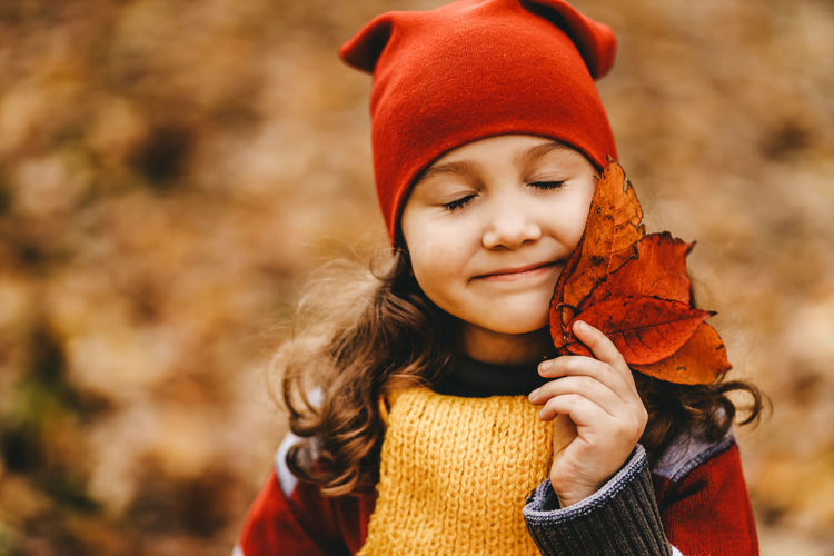 Portrait of a little girl a child in a warm hat walking holding an autumn foliage in the fall forest