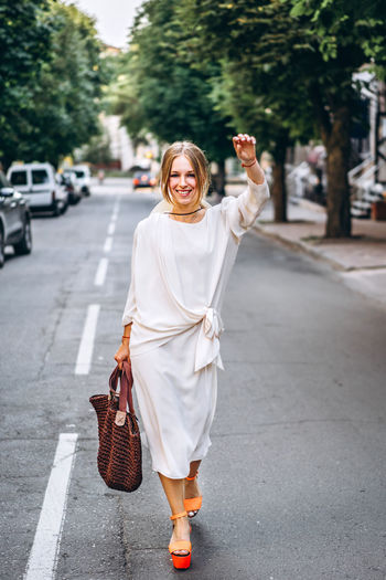 One Person Full Length Looking At Camera Real People Smiling Portrait Women City Young Adult Front View Focus On Foreground Happiness Road Lifestyles Adult Emotion Holding Street Day Outdoors Human Arm Beautiful Woman