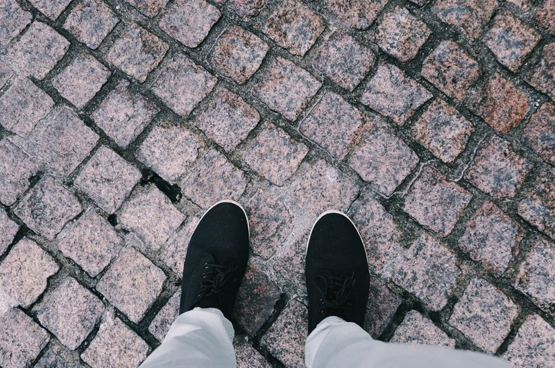 Low section of person standing on cobblestone