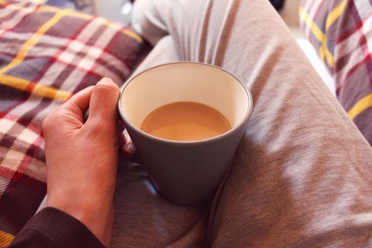 Midsection of person holding coffee cup on lap