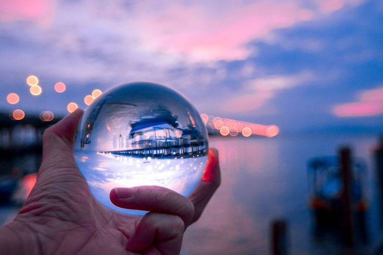 Cropped hand holding crystal ball by sea during sunset