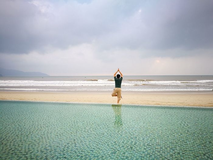 Rear view of man exercising amidst swimming pool and sea at beach