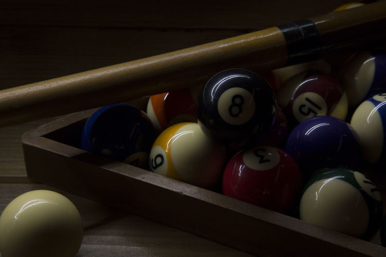 Close-Up Of Balls With Rack And Pool Cue On Table