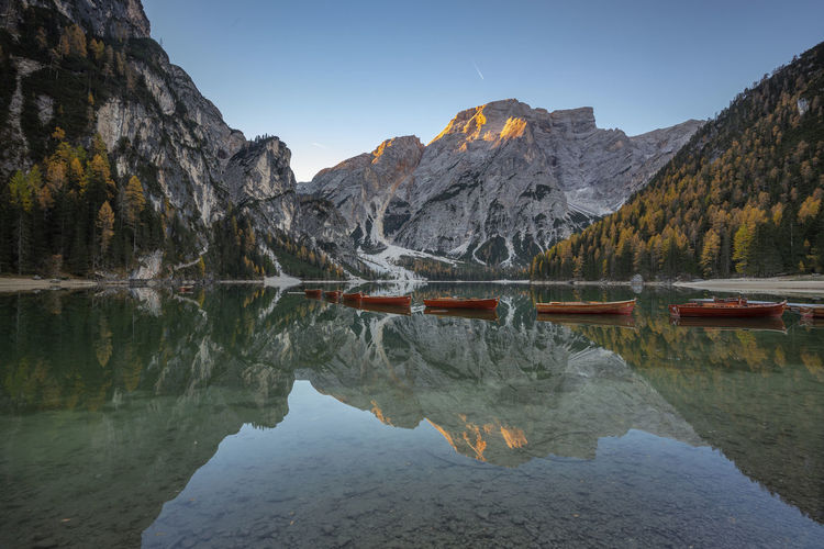 Perfect mirroring in autumn colors at Lake Braies, Dolomites Mountain Reflection Water Scenics - Nature Sky Beauty In Nature Nature Tranquility Mountain Range Tranquil Scene Lake Waterfront No People Day Idyllic Non-urban Scene Rock Symmetry Standing Water Outdoors Formation Eroded Mountain Peak Sunrise Dolomites, Italy