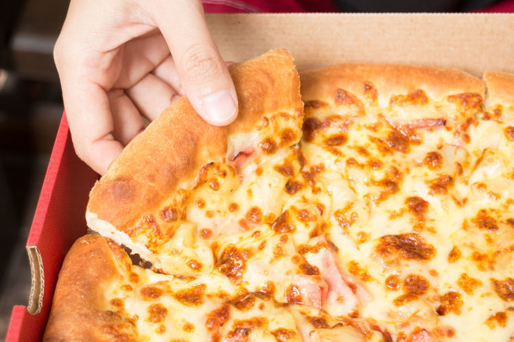 Cropped hand holding pizza